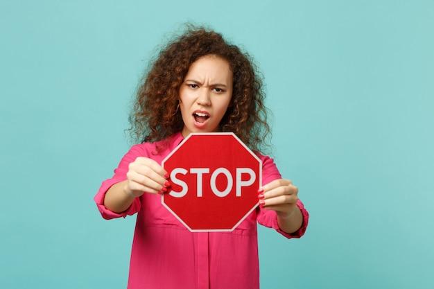 Ritratto di una ragazza africana irritata in abiti casual rosa che tiene la scheda di testo stop isolata su sfondo blu turchese parete in studio. concetto di stile di vita di emozioni sincere della gente. mock up copia spazio.