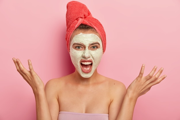 Portrait of irritated female model screams with annoyance, has beauty treatments, raises palms, gestures angrily, applies nourishing clay mask on face, wears bath towel on head, isolated on pink wall