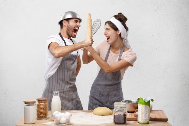 Portrait of irritated male fights with wife uses rolling pin and whisk.