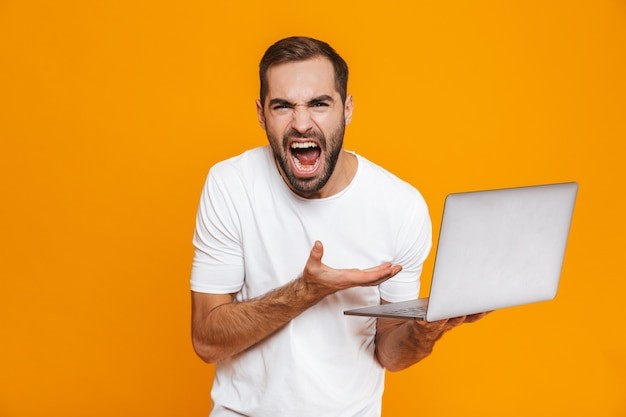Portrait of irritated man 30s in white t-shirt screaming and holding silver laptop, isolated