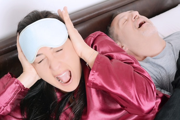 Portrait of irritated woman blocking ears with hands while man snoring on bed