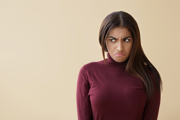 Portrait of irritated young african american beautiful lady frowning and looking away with grumpy expression, feeling displeased with something. anger, annoyance, irritation and negative emotions