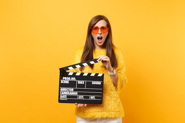 Portrait of irritated young woman in fur sweater orange heart glasses holding classic black film making clapperboard isolated on yellow background. people sincere emotions lifestyle. advertising area.