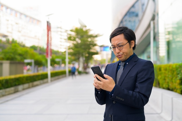 Portrait of japanese businessman getting fresh air with nature in the city outdoors