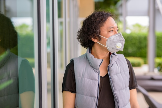 Portrait of japanese man with curly hair wearing mask for protection from coronavirus outbreak in the city outdoors