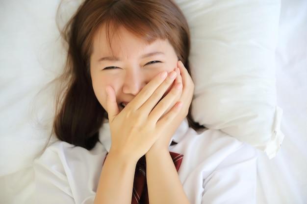 Портрет японская школьница спит и улыбается в белой комнате