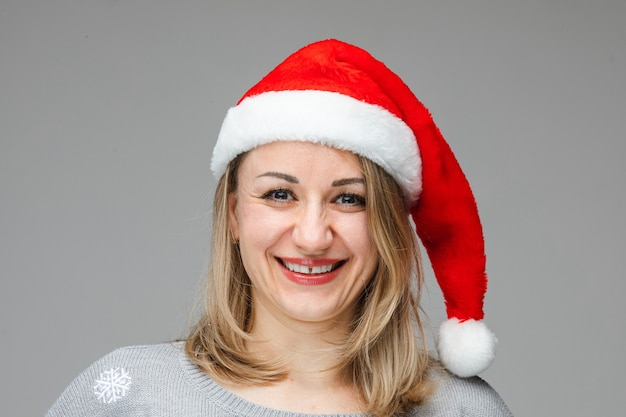 Portrait of jovial blonde caucasian woman wearing red santa hat with white rim