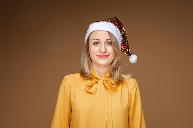 Portrait of jovial blonde caucasian woman in yellow blouse wearing sparkling santa hat