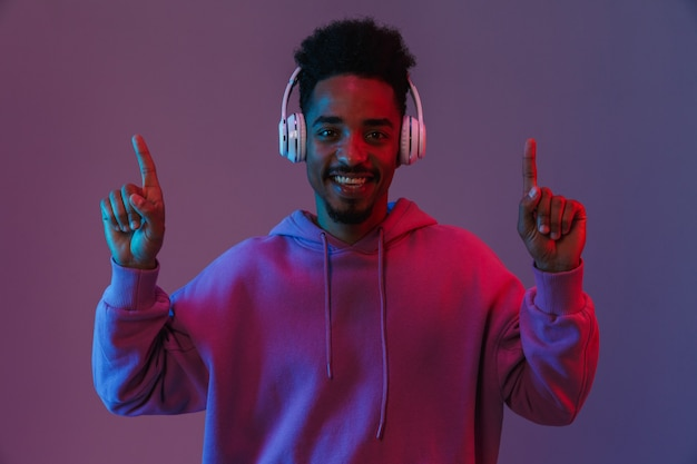 Portrait of joyful african american man listening to music with headphones and pointing fingers upward isolated over violet wall