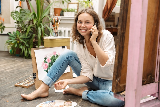 Portrait of joyful artistic woman sitting on floor and talking at cellphone while drawing picture on paper with paint palette in workshop or master class