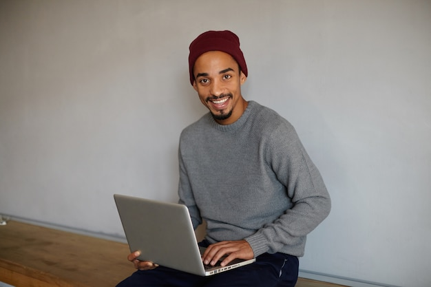Portrait of joyful attractive dark skinned bearded guy working remotely with modern laptop, sitting on wooden bench and smiling cheerfully, wearing casual clothes