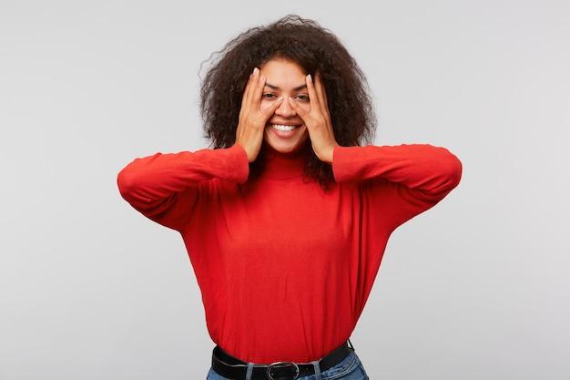 Ritratto di gioiosa donna attraente e felice in maniche lunghe rosse con acconciatura afro alla moda, che copre gli occhi con le palme