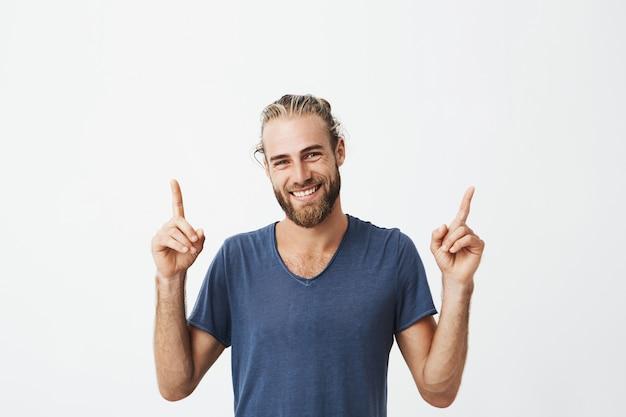 Ritratto di bei uomini allegri con l'acconciatura alla moda e la barba in maglietta blu che ride e che indica su