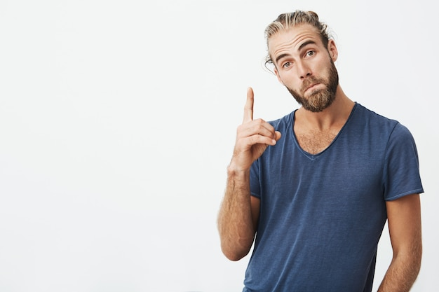 Ritratto di gioiosi uomini belli con acconciatura alla moda e barba, rivolto verso l'alto