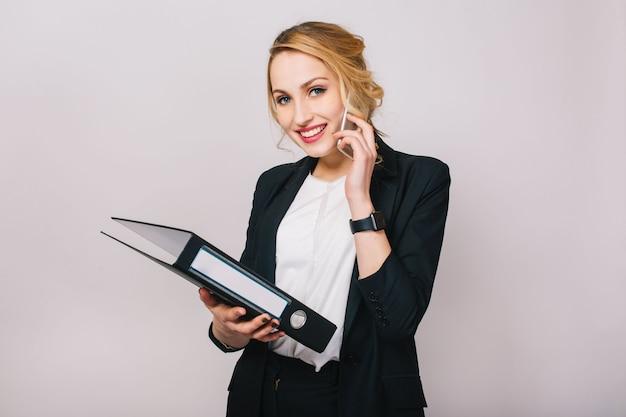 Портрет радостной блондинки бизнесмен разговаривает по телефону, держа папку, улыбаясь изолированы. в белой рубашке и черной куртке, современный офисный работник, элегантный, карьера