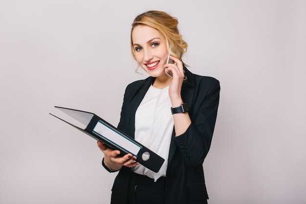 Portrait joyful blonde businesswoman talking on phone, holding folder, smiling isolated. wearing white shirt and black jacket, modern office worker, elegant, career