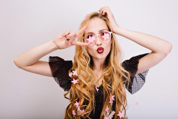 Ritratto di gioiosa bionda con lunghi capelli ricci divertendosi alla festa, facendo una faccia buffa, mostrando pace, bacio, godendo della celebrazione. indossa un abito nero, occhiali rosa. isolato..
