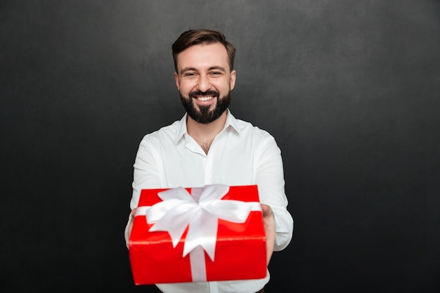 Portrait of joyful brunette man showing red present box on camera and smiling over dark gray wall