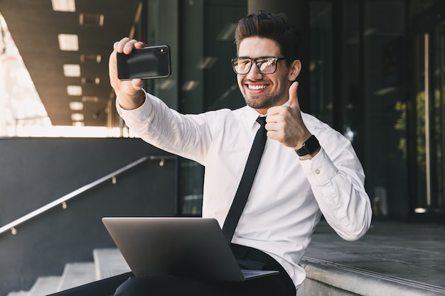 Portrait of joyful businessman dressed in formal suit sitting outside glass building with laptop, and taking selfie photo on smartphone