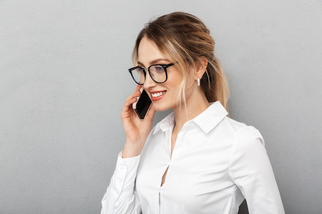 Portrait of joyful businesswoman wearing glasses smiling and speaking on mobile phone in the office, isolated