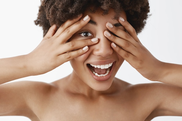 Ritratto di gioiosa e spensierata splendida donna dalla carnagione scura con i capelli ricci, che copre la vista con i palmi delle mani e sbircia tra le dita scherzosamente, posa nuda sul muro grigio