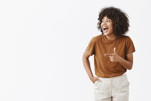 Portrait of joyful charming carefree african american woman with curly hairstyle looking and pointing left with finger gun laughing from happiness and good mood