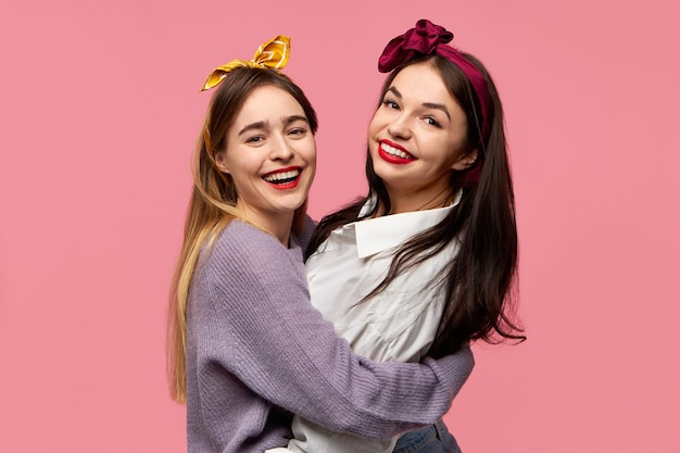 Portrait of joyful charming young caucasian female friends having fun, laughing, being in good mood embracing each other isolated against pink wall background