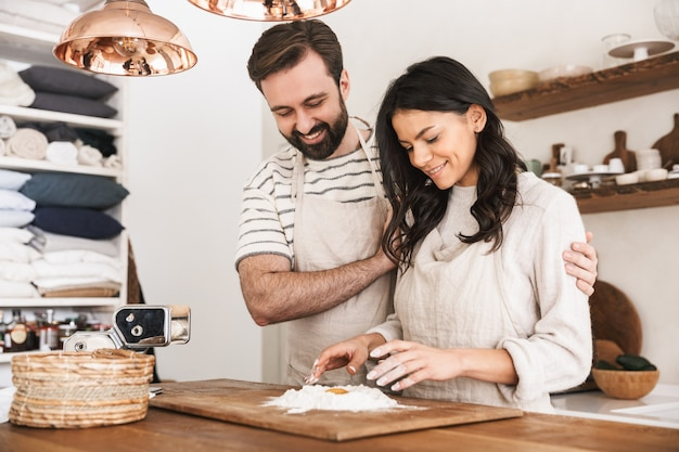 Portrait of joyful couple man and woman 30s wearing aprons cooking pastry with flour and eggs in kitchen at home