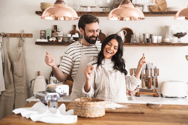 Portrait of joyful couple man and woman 30s wearing aprons enjoying cook together in kitchen at home