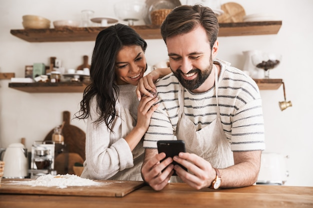 Portrait of joyful couple man and woman 30s wearing aprons reading recipe while cooking pastry with flour and eggs in kitchen at home