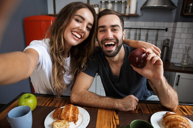 Portrait of joyful couple man and woman taking selfie photo on cell phone while having breakfast in kitchen at home