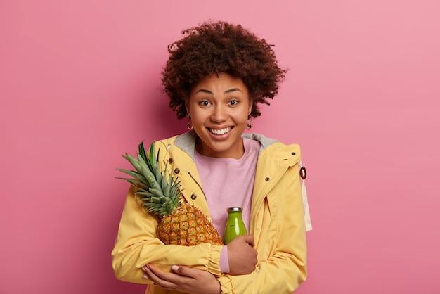 Ritratto di donna riccia gioiosa abbraccia ananas fresco e succoso e frullato verde a base di frutta, indossa una giacca a vento gialla, sorride positivamente