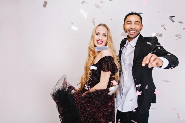 Портрет радостной милой пары в любви, празднующей большую вечеринку в мишурах. роскошная вечерняя одежда, счастье, улыбка
