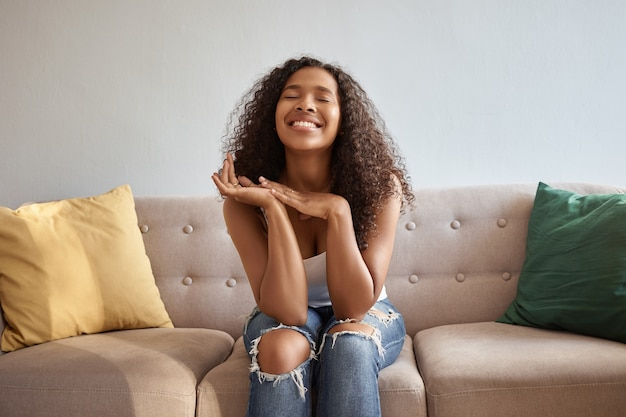 Portrait of joyful emotional young dark skinned female posing in living room on comfortable couch, sitting in stylish ragged jeans, looking up with hands under her chin, being in good mood, smiling