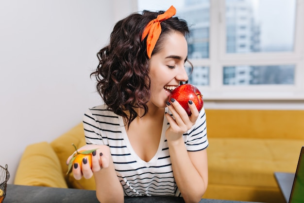 Portrait joyful excited young woman with curly cut hair enjoying red apple in modern apartment. smiling, having fun, chilling at home, cosiness, relax, happiness
