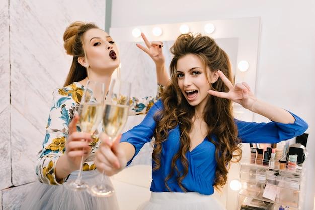 Giovani donne eccitate gioiose del ritratto che hanno divertimento nel salone del parrucchiere
