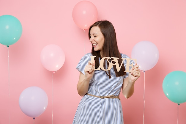 Portrait of joyful fascinating young woman in blue dress looking aside holding wooden word letters love on pink background with colorful air balloons. birthday holiday party people sincere emotions.
