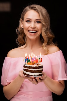 Portrait of joyful fashion woman posing holding cake candles happy birthday