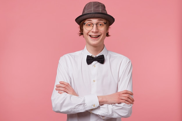 Portrait of joyful funny young guy in white shirt, hat and black bowtie wears glasses happily laughing showing orthodontic brackets,standing with hands crossed, isolated on pink background