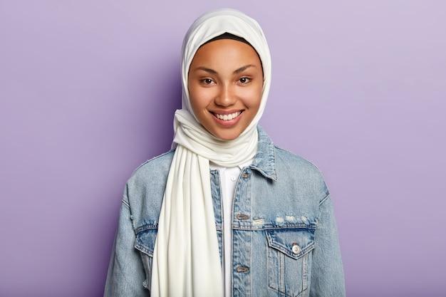 Ritratto di donna gioiosa di bell'aspetto ha opinioni islamiche, sorride delicatamente alla telecamera