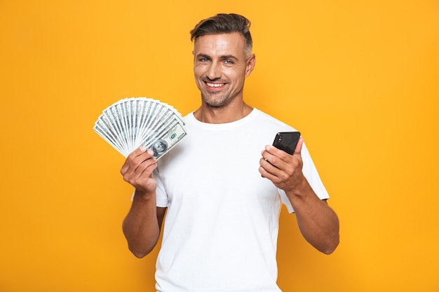Portrait of joyful guy 30s in white t-shirt holding cell phone and bunch of money isolated on yellow