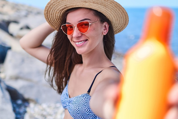 Portrait of a joyful happy smiling woman in a swimsuit, straw hat and red sunglasses with a bottle of sun block cream while sunbathing by sea in the summer