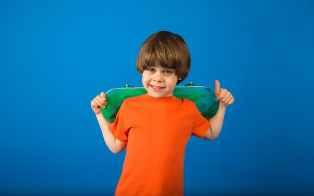 Portrait of a joyful little boy in an orange t-shirt holding a skateboard on a blue surface with a copy of the space