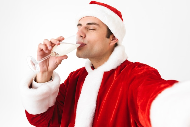 Portrait of joyful man 30s in santa claus costume and red hat taking selfie photo while holding glass with champagne