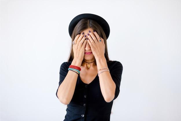 Portrait joyful pretty woman covering her eyes