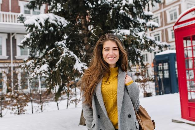肖像画うれしそうな笑顔の若い女性が街の通りを歩いて、寒い冬の天候。ファッショナブルなモデル、陽気な感情、雪の時間