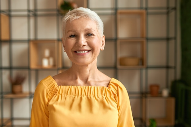 Portrait of joyful stylish middle aged woman with short haircut posing indoors expressing positive emotions