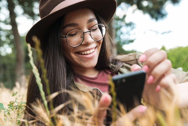 Portrait of joyful stylish woman with long dark hair wearing hat and eyeglasses using cellphone while lying on grass in green park