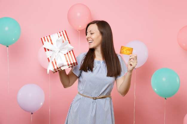 Portrait of joyful tender woman in blue dress holding credit card and red box with gift present on pastel pink background with colorful air balloons. birthday holiday party, people sincere emotions.