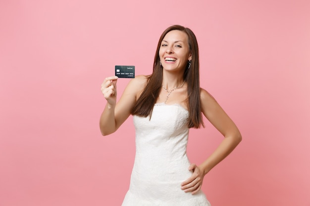 Portrait of joyful woman in beautiful lace white dress holding credit card